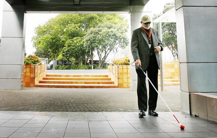 A man walking with a white cane