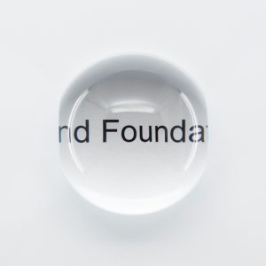 "Solid glass dome magnifier over the text ""Blind Foundation"""