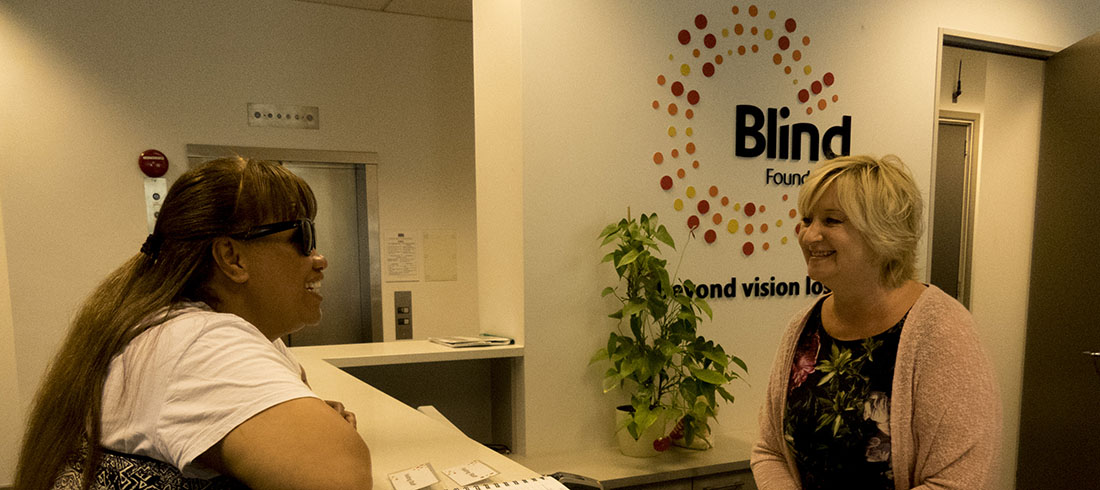 A woman chats to the receptionist at a Blind Foundation office.