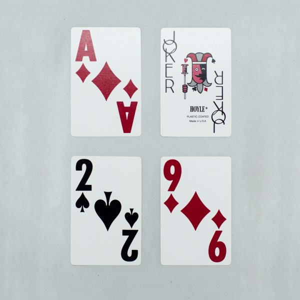 Four low vision playing cards with large print numbers and symbols