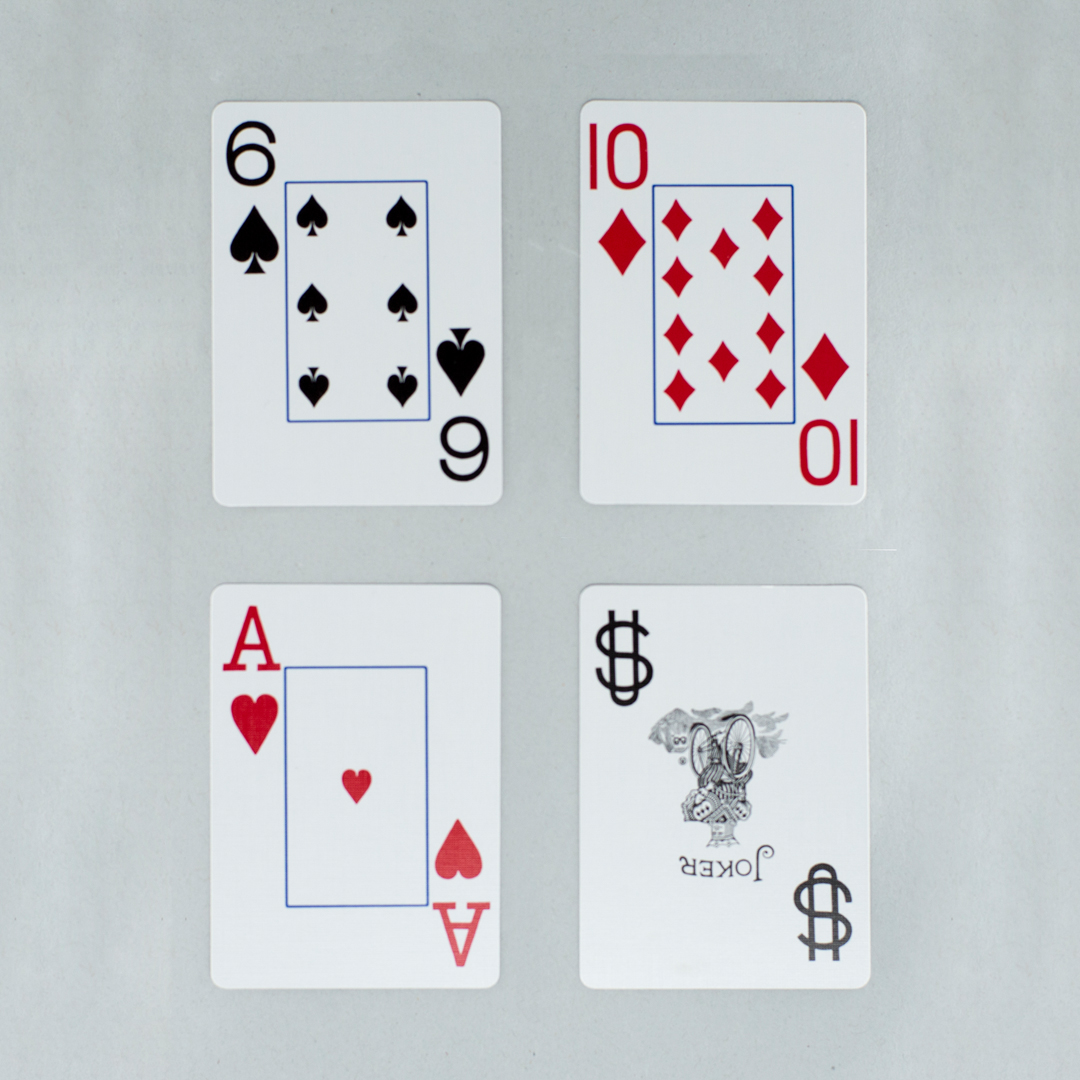 Four jumbo sized playing card with large print numbers and symbols