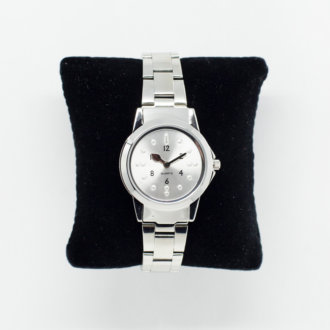 Silver tactile wrist watch on a black pillow