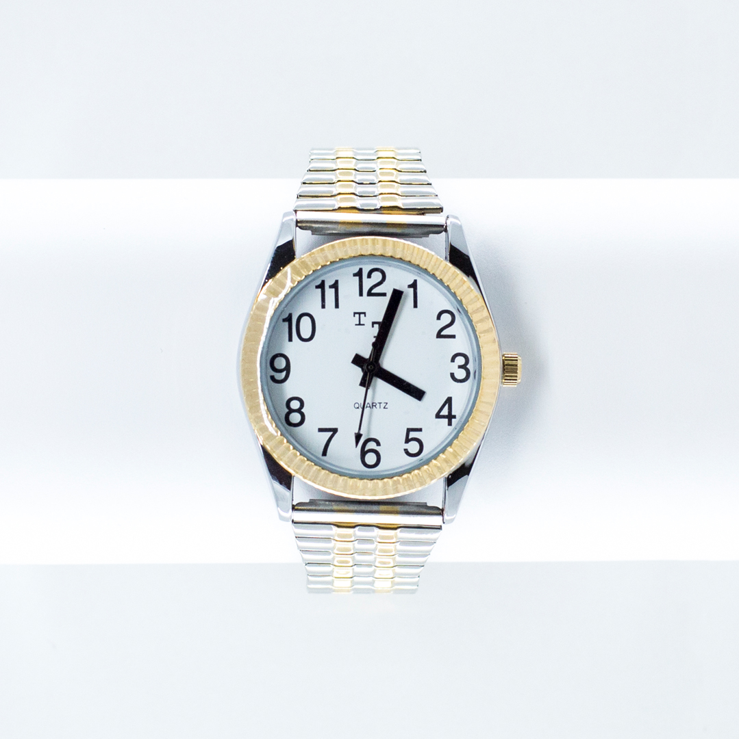 Gold and chrome watch with a white face and large print black numbers