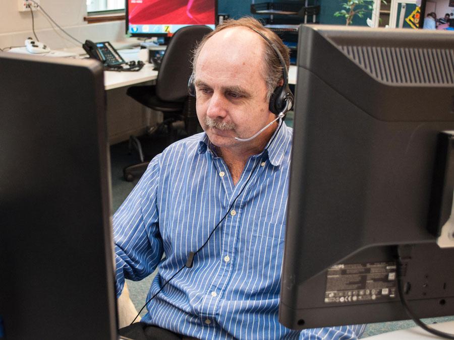 A man in an office wearing a headset
