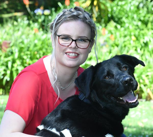 Stevi hugging her guide dog Halo