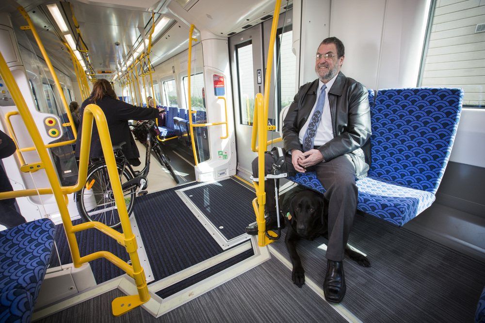 Blind Foundation Access and Awareness Advisor Chris Orr and guide dog Noble on-board an electric train.