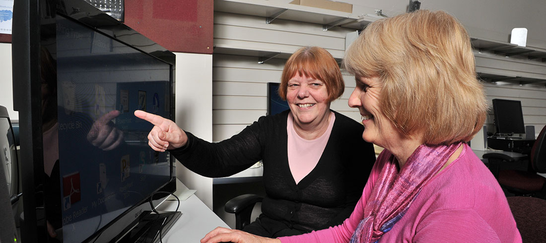 One woman shows another woman something on a computer screen.