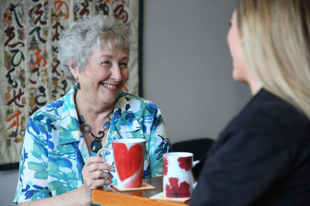 Two women chat over a cup of tea.