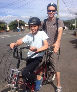 Toby and his Dad on a tandem bike. Dad has a tshirt with braille.