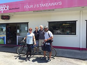Asima Leone and his wife Catheriane take photo with Mr Four J's at the Four J's Takeaways