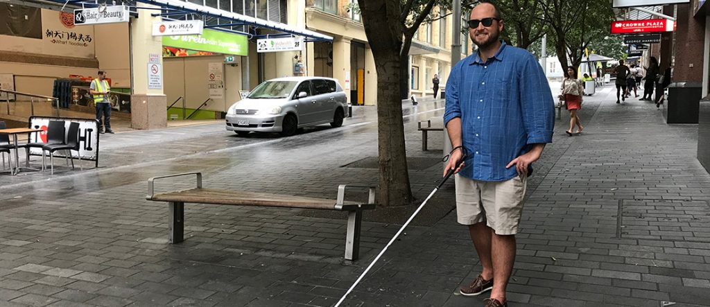 Dan Shepherd holds his white cane on Elliot Street, Auckland.