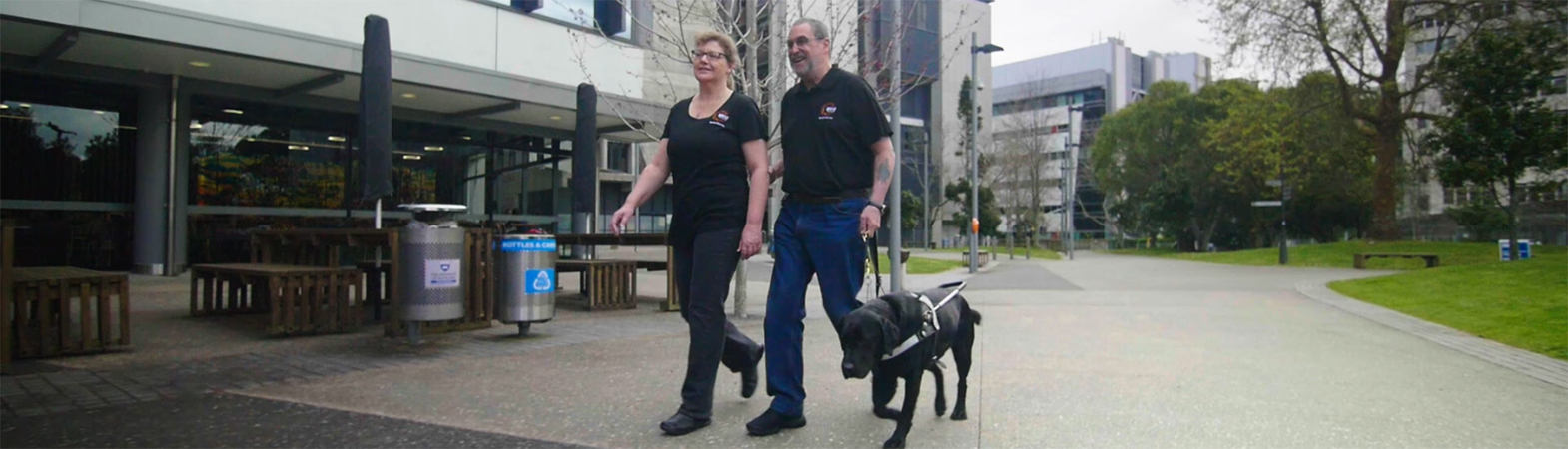 A lady is guiding a man who walking with a guide dog