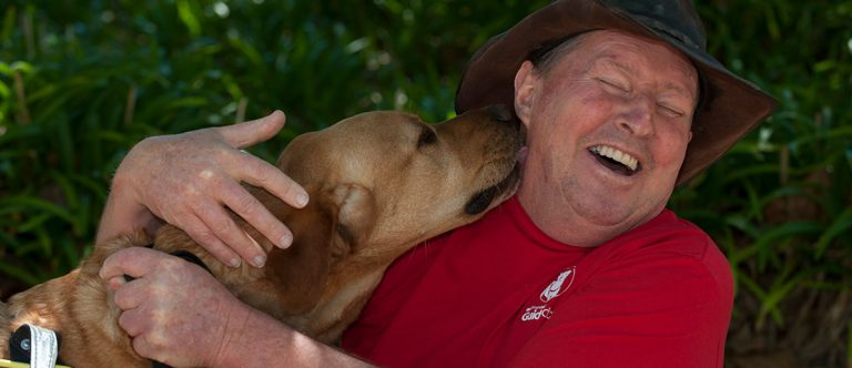 A man being kissed by his dog