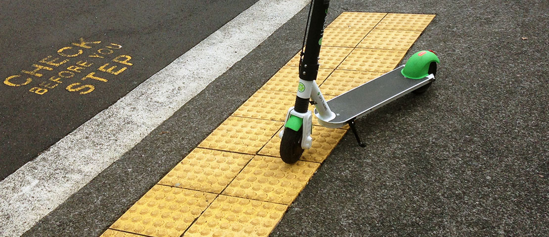 A e-scooter is parking on the yellow tactile blocks