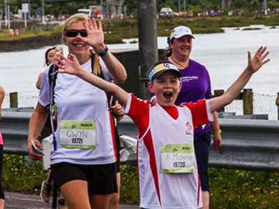 Alex and his mum wave their hands when they are running