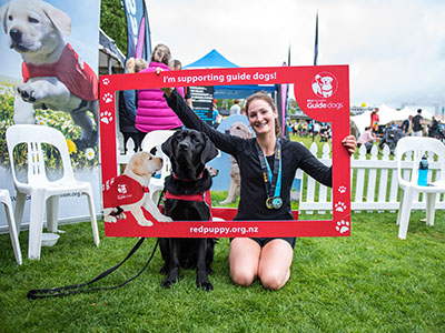 Lucy hold the support guide dog sign with a black guide dog at the Auckland Marathon