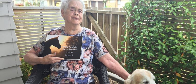 Judy sit with her guide dog and hold the book 'Bright sunlight, dark shadow'