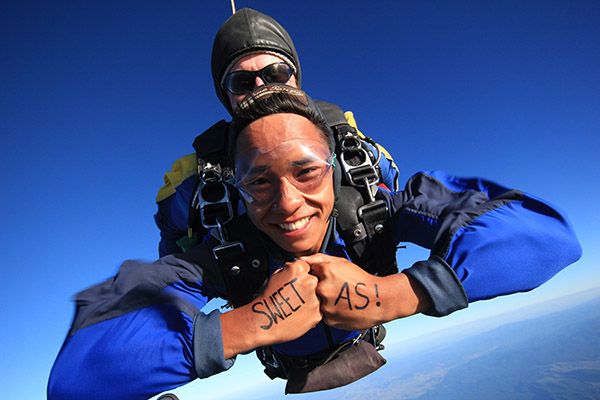 A man skydiving with message sweet as on his hands