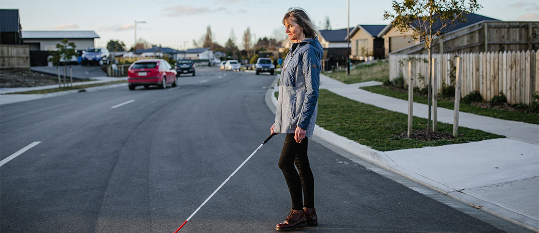 Sue crossing the road using a white cane