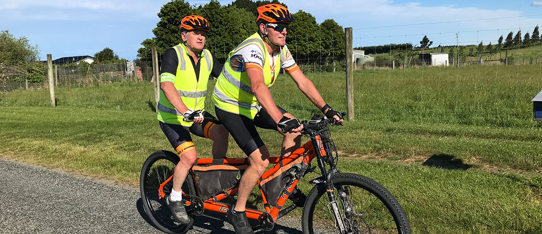 Paul Glass and his tandem bike captain Russell Shanks riding on a country road