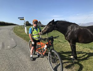 Paul Glass sits on his tandem bike while a friendly horse says hello