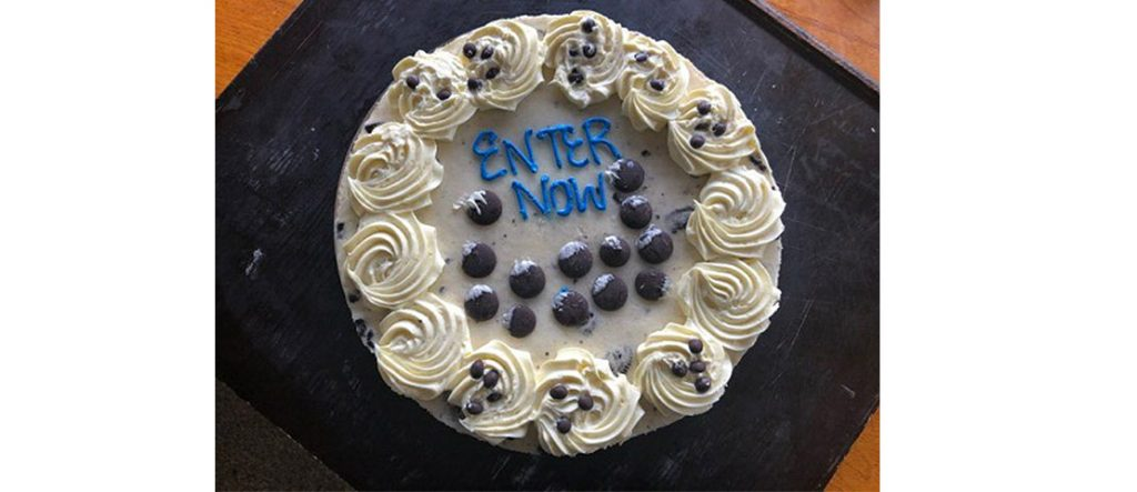 Cake reads 'enter now' with chocolate buttons
