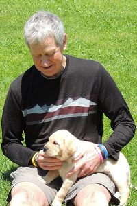 Stewart playing with a guide dog puppy in training.
