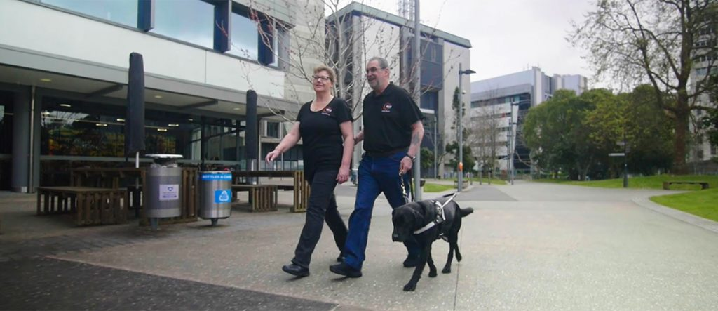 A volunteer guiding our client with a guide dog