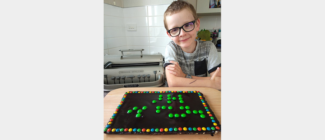 Zach with his chocolate slice with M&Ms spelling 'braille is fun'
