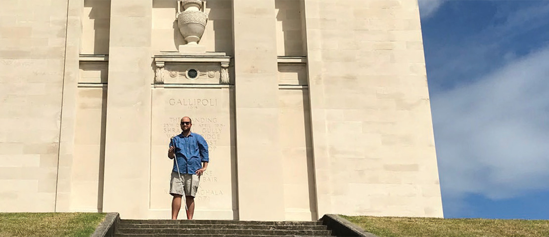 Dan Shepherd holds his white cane at the top of the Auckland Museum steps