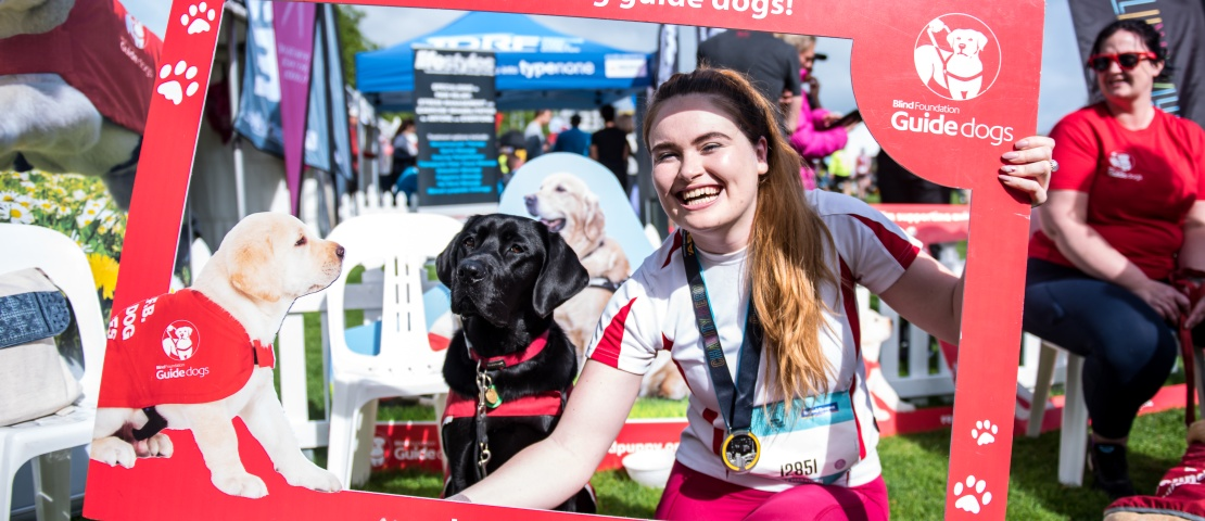 An Auckland marothon runner takes a huge red guide dog photo frame with a guide dog