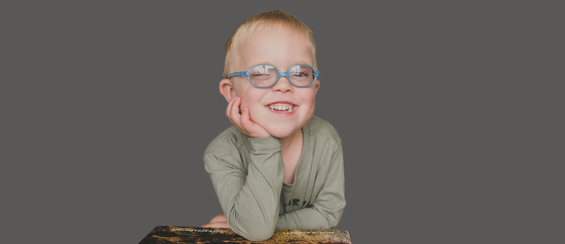 Little William, age 4, with blonde hair and blue glasses sits at a desk and smiles.