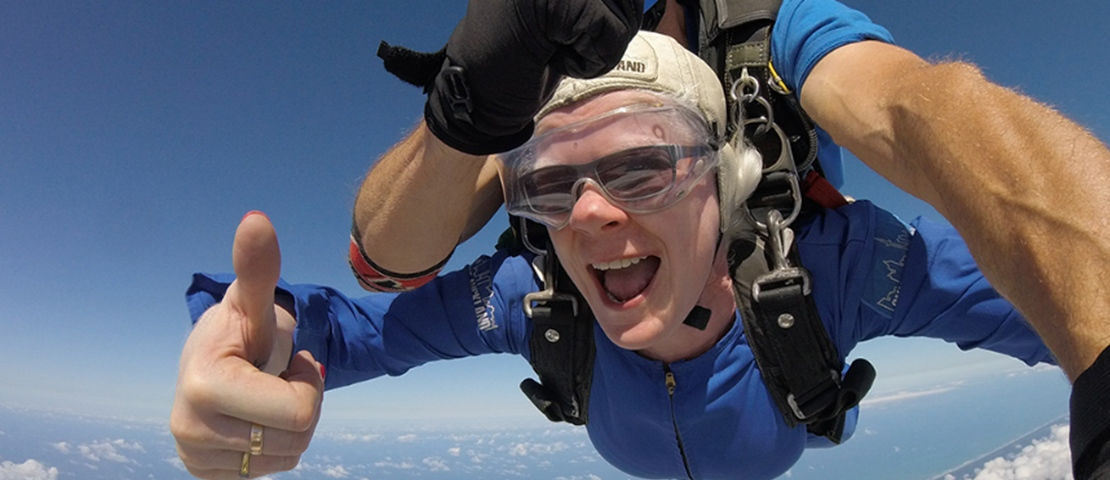 A woman is doing tandem skydiving with thumb up
