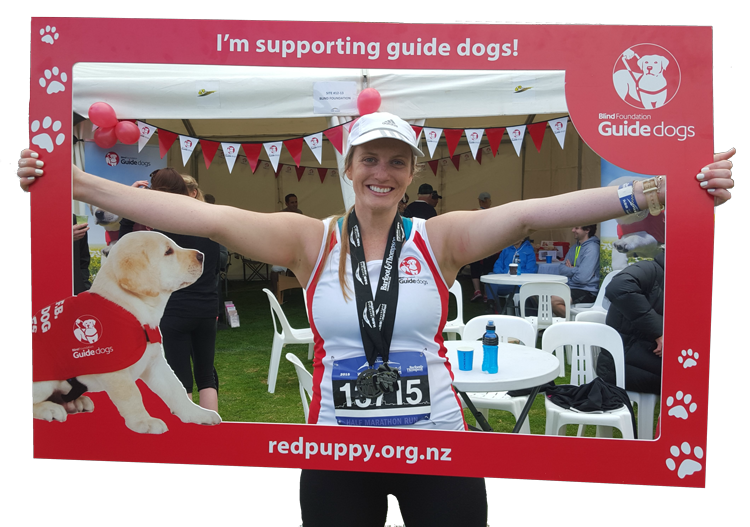 A marathon runner holding up the guide dogs picture frame