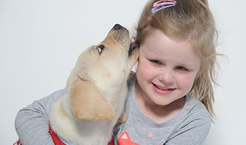 Puppy licking little girls face
