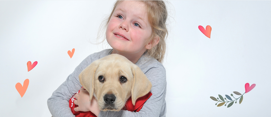 A young girl cuddling a yellow Labrador puppy