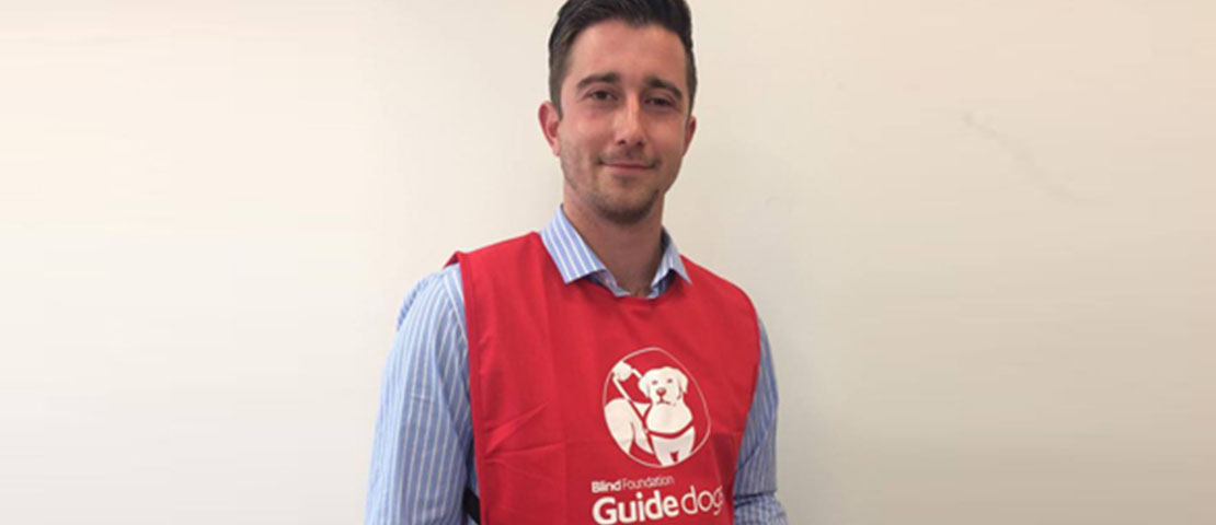 A man wearing a red guide dogs bib and holding an iPad