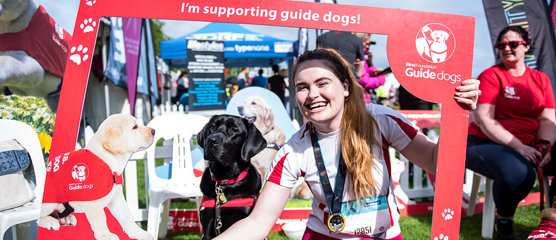 A woman who hold a red photo frame with a black guide dog at Auckland Marathon