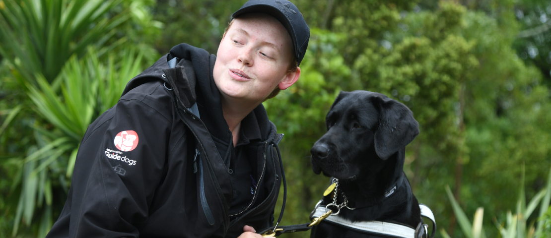 a guide dog trainer sit with a guide dog
