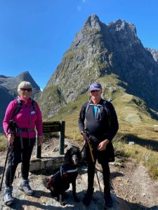 Neville, Jenny and guide dog Sophie in front of a mountain pass.