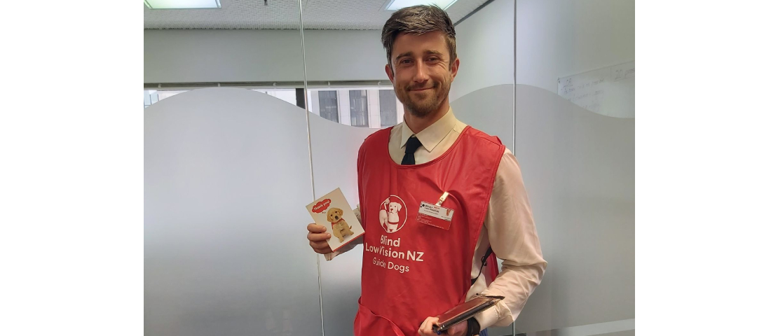 Blind Low Vision NZ fundraiser wearing a red vest and holding an iPad