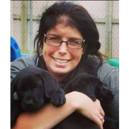 Trudy smiling at the camera while holding two black guide dog puppies in her arms.