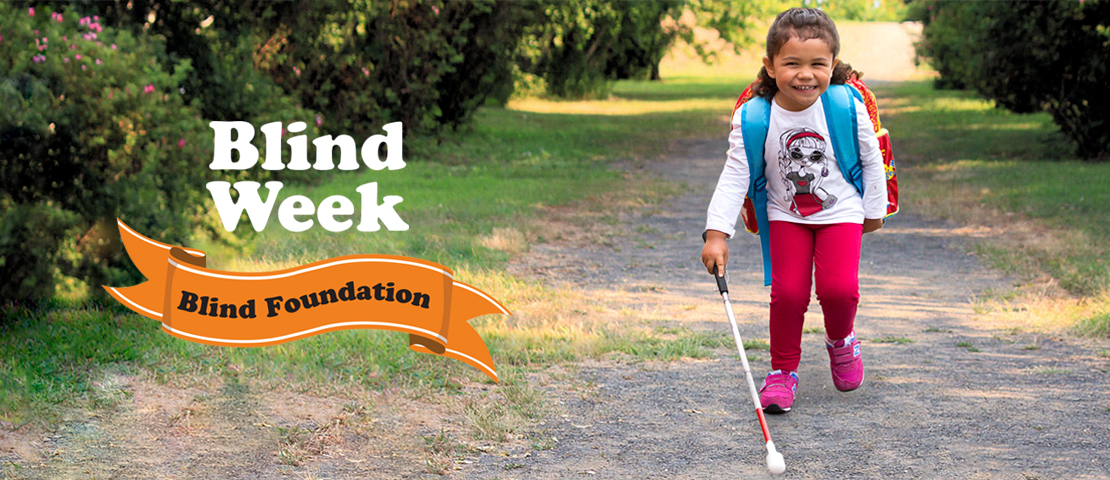A young girl walking down a path with a white cane