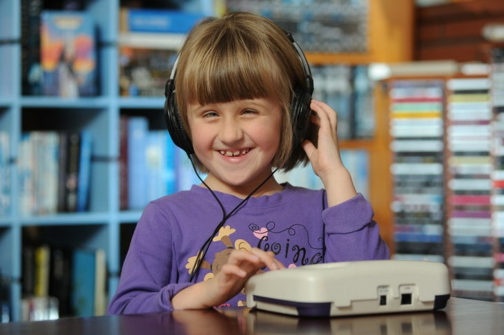 A young girl listening to an audio book through a DAISY player
