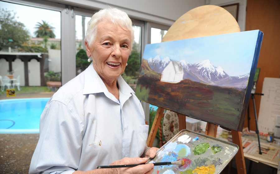 A woman painting a landscape scene