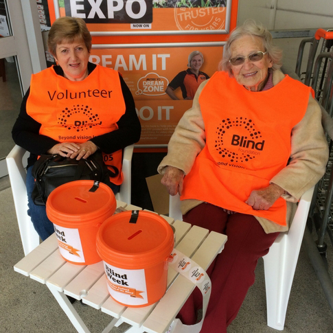 Two woman in orange Blind Week collection bibs outside Mitre 10